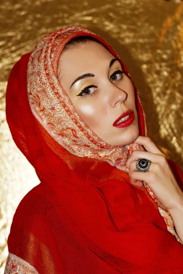 Jeune femme Arabe Maquillage d'or Hijab ethnique rouge de châle de vêtements, accessoires image stock