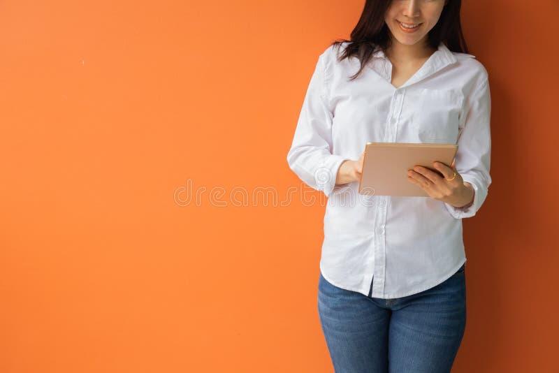 Jeune femme asiatique à l'aide du comprimé, smartphone, téléphone portable sur le fond orange d'isolement photo stock