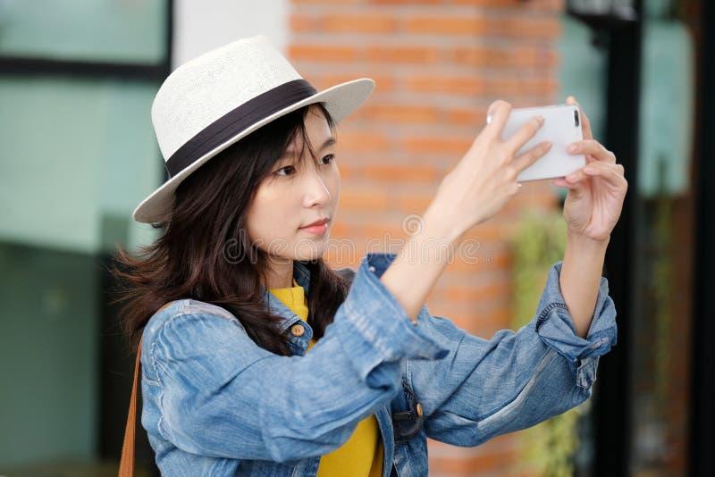 Jeune femme asiatique à l'aide du téléphone intelligent à l'arrière-plan d'extérieur de ville, les gens extérieurs avec la techno photos stock
