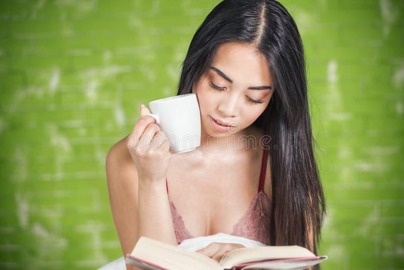 Jeune femme asiatique affichant un livre images stock