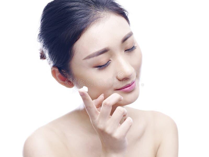 Jeune femme asiatique appliquant la lotion au visage images libres de droits