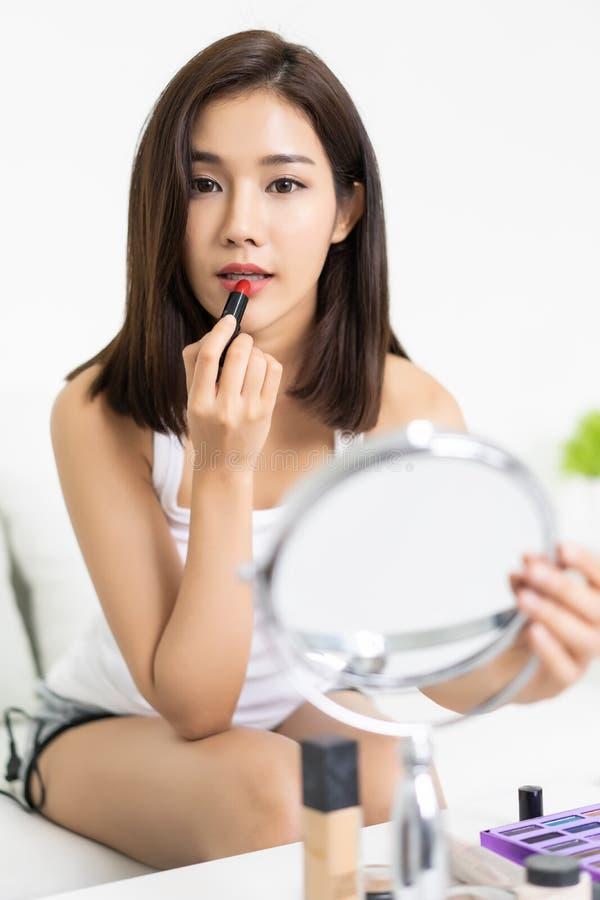 Jeune femme asiatique appliquant le rouge à lèvres sur son sofa dans la chambre à coucher l images stock