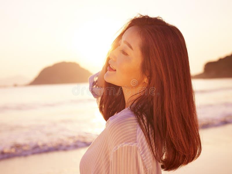 Jeune femme asiatique appréciant la lumière du soleil de matin photos libres de droits