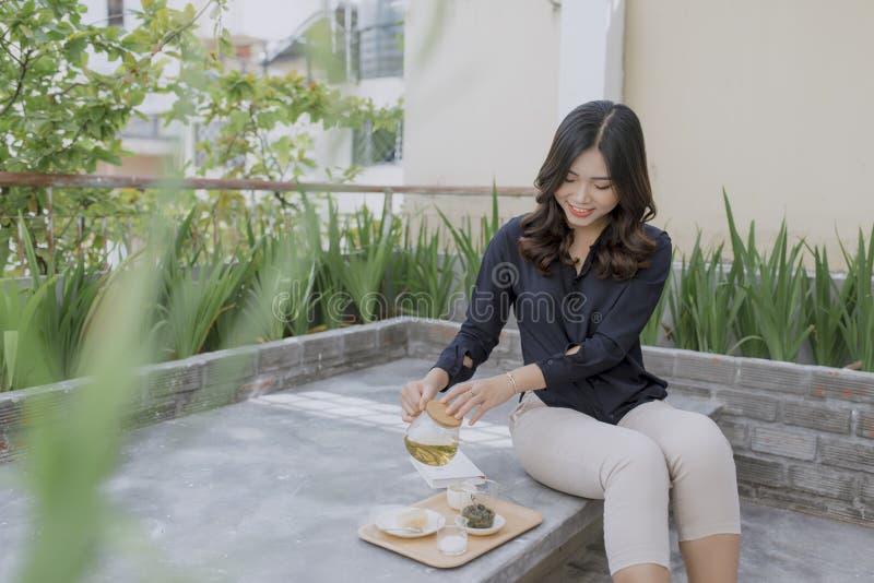 Jeune femme asiatique appréciant sa terrasse confortable image libre de droits
