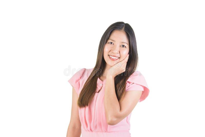 Jeune femme asiatique attirante de sourire utilisant le contact de main la joue photographie stock libre de droits