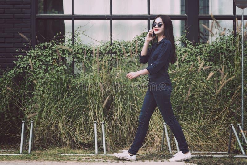 Jeune femme asiatique attirante en passant marchant et parlant sur elle images libres de droits