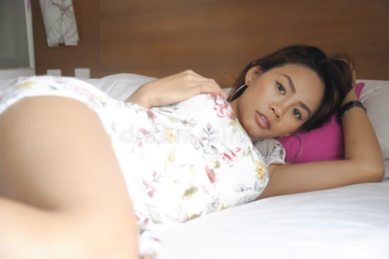 Jeune femme asiatique attirante et belle se trouvant sur le lit à la pose de chambre à coucher sexy dans l'ensemble de studio de  photos libres de droits