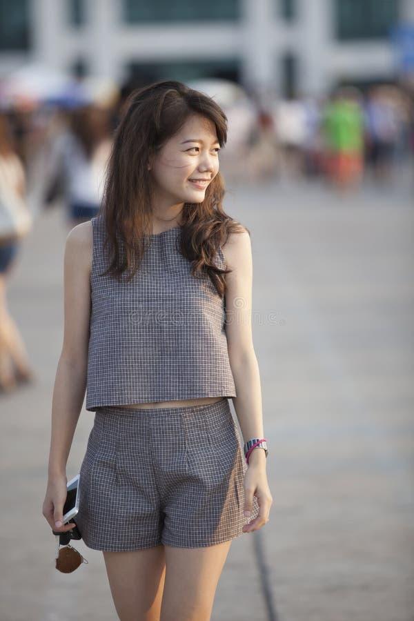 Jeune femme asiatique attirante marchant porte avec la détente et photo stock