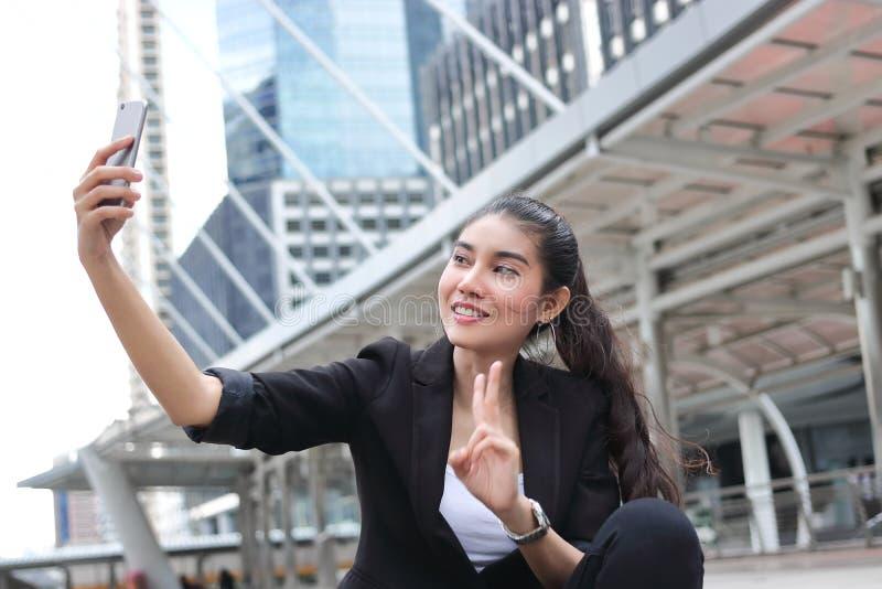 Jeune femme asiatique attirante prenant une photo ou un selfie avec le téléphone intelligent mobile sur la rue de la ville modern photos libres de droits
