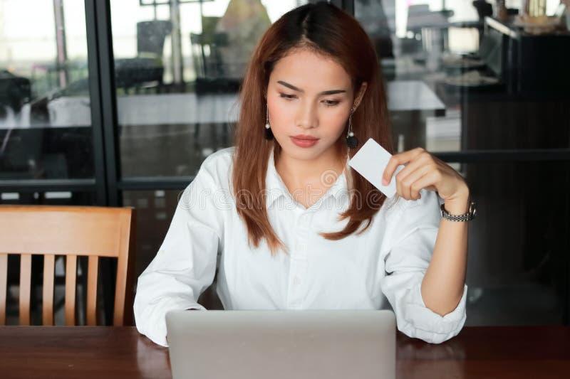 Jeune femme asiatique attirante tenant la carte de crédit avec l'ordinateur portable dans le salon Concept en ligne d'achats image stock
