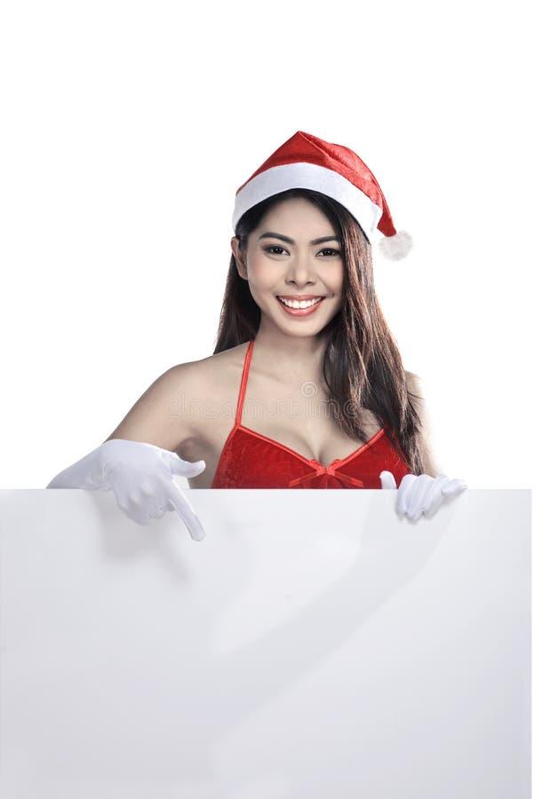 Jeune femme asiatique attirante utilisant le costume de Santa Claus tenant le panneau d'affichage vide image libre de droits