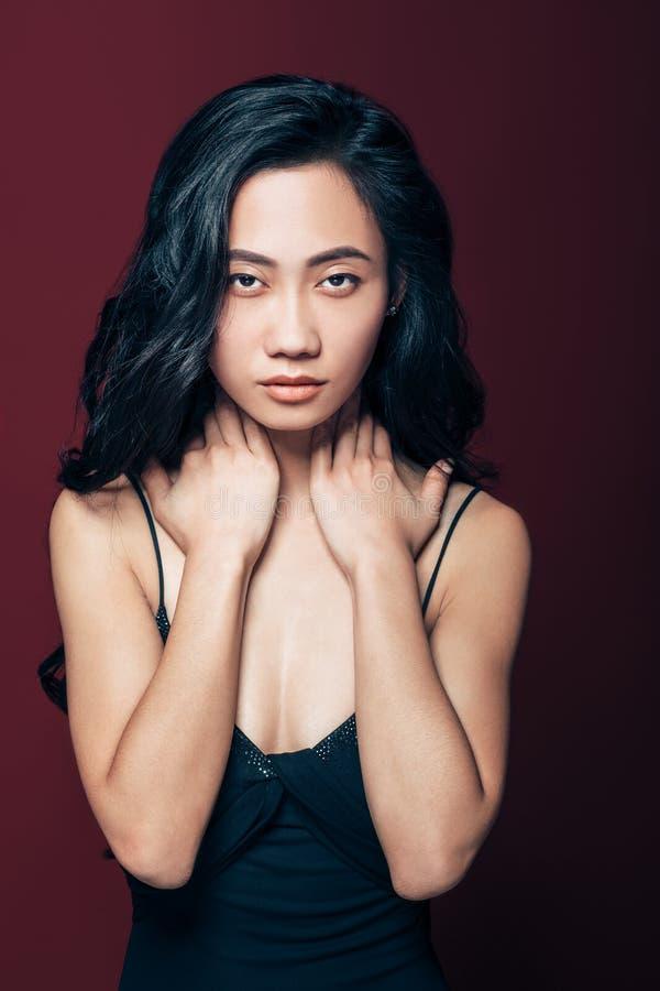 Jeune femme asiatique avec des mains sur le cou regardant l'appareil-photo images libres de droits