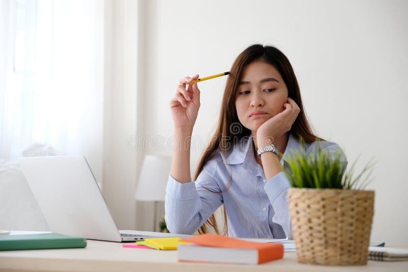 Jeune femme asiatique avec l'expression frustrante tout en travaillant avec l'ordinateur portable, fonctionnant du mode de vie à  images libres de droits