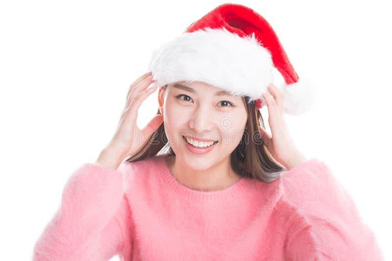 Jeune femme asiatique avec le chapeau de Noël d'isolement sur le blanc photo libre de droits