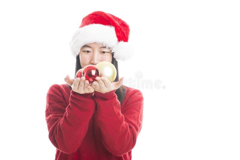 Jeune femme asiatique avec le chapeau de Noël d'isolement sur le blanc image stock