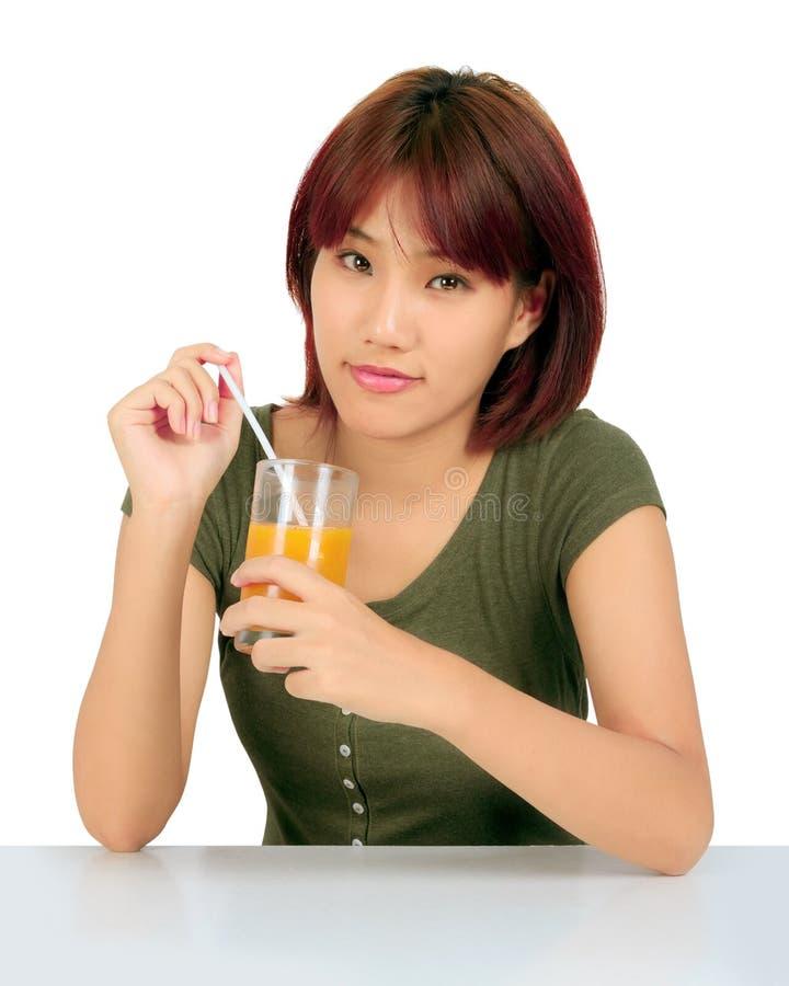 Jeune femme asiatique avec un verre de jus d'orange photographie stock libre de droits