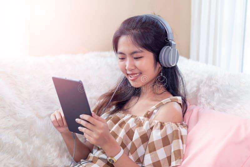 Jeune femme asiatique avoir plaisir à écouter la musique avec des écouteurs et à employer le temps de comprimé, heureux et de dét photographie stock libre de droits