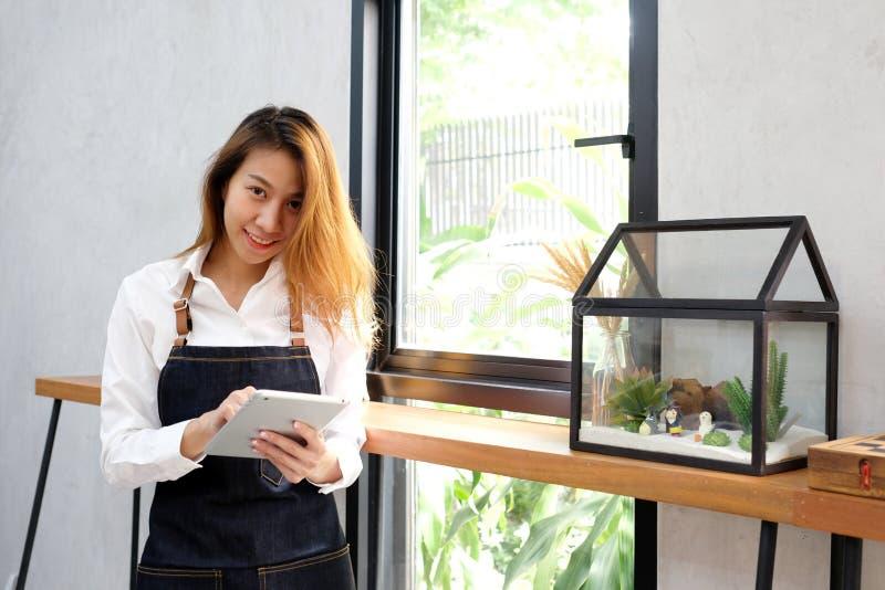 Jeune femme asiatique, barman, utilisant le comprimé pour obtenir l'ordre de café au fond de compteur de café, à la nourriture et photo libre de droits