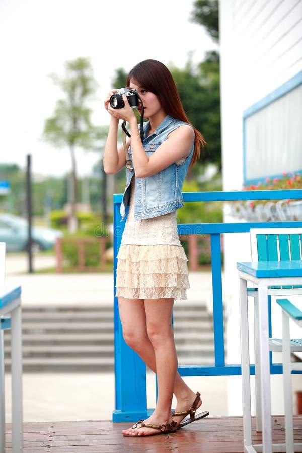 Jeune femme asiatique célibataire avec l'appareil-photo photos stock