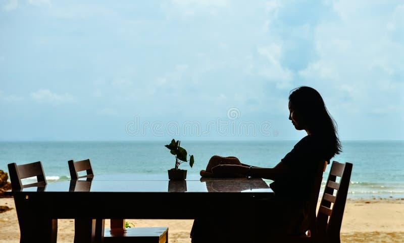 Jeune femme asiatique célibataire s'asseyant à la table de salle à manger sur la plage image libre de droits