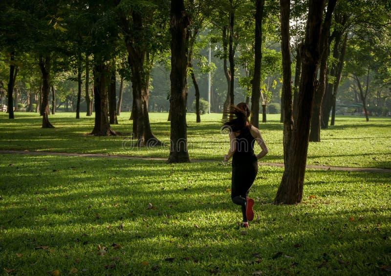 Jeune femme asiatique courant en parc images stock