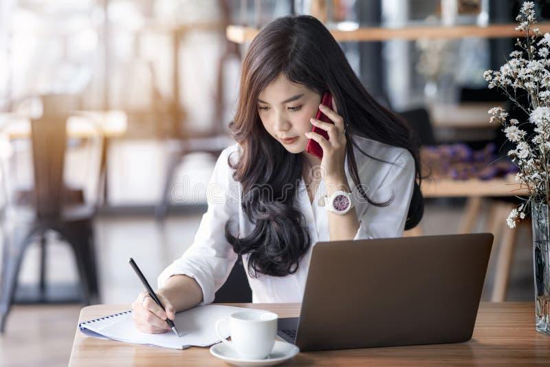 Jeune femme asiatique d'affaires à l'aide de l'ordinateur portable et écrivant sur le carnet image libre de droits