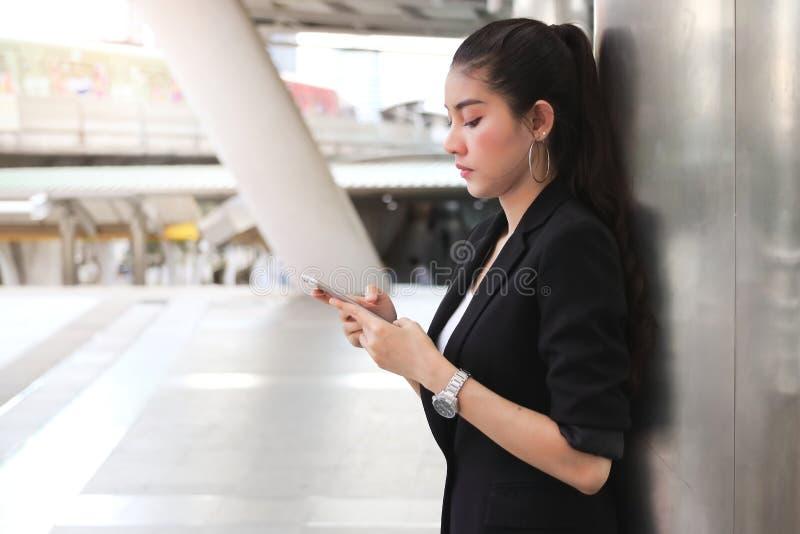 Jeune femme asiatique d'affaires avec le téléphone intelligent mobile à l'arrière-plan urbain Internet de concept de choses photos stock