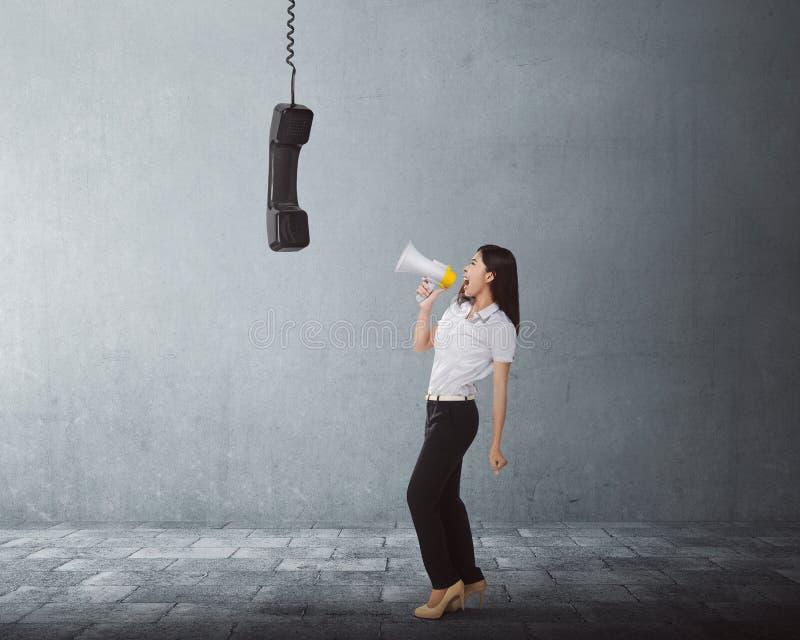 Jeune femme asiatique d'affaires criant utilisant un mégaphone pour noircir photo stock