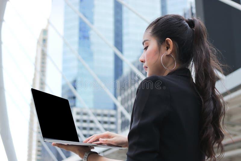 Jeune femme asiatique d'affaires de direction travaillant avec le fond moderne de gratte-ciel d'ordinateur portable photo libre de droits