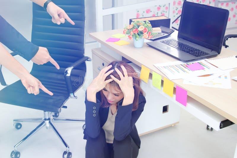 Jeune femme asiatique d'affaires de renversement frustrant avec des doigts se dirigeant à elle dans le lieu de travail du bureau image stock