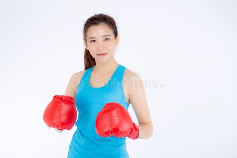 Jeune femme asiatique de beau portrait portant les gants de boxe rouges avec la force et la force d'isolement sur le fond blanc,  photographie stock