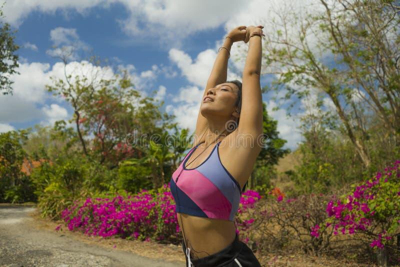 Jeune femme asiatique de coureur attrayant et sain s'étirant et respirant pour frais ou réchauffer pendant la séance d'entraîneme photo stock