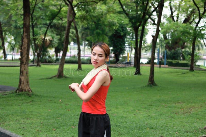 Jeune femme asiatique de forme physique étirant ses mains avant course en parc Séance d'entraînement et concept d'exercice photo libre de droits