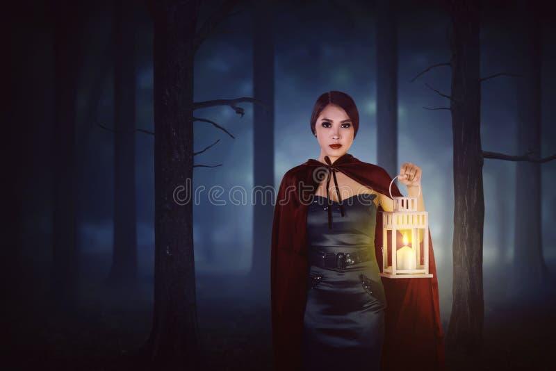 Jeune femme asiatique de sorcière avec le manteau rouge marchant dans la forêt avec a image stock
