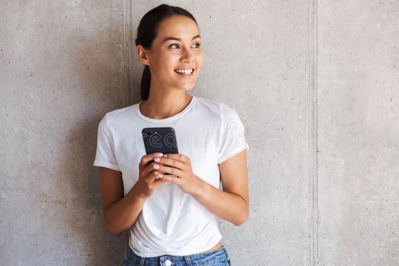 Jeune femme asiatique de sourire à l'aide du téléphone portable photo stock