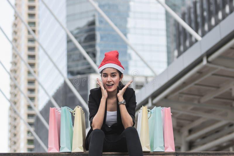 Jeune femme asiatique de sourire avec le chapeau de Santa et le panier coloré se reposant dehors après l'achat pour des cadeaux d photographie stock