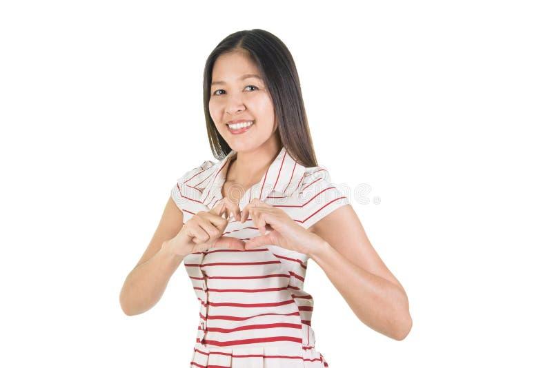 Jeune femme asiatique de sourire heureuse faisant la forme de coeur photo stock