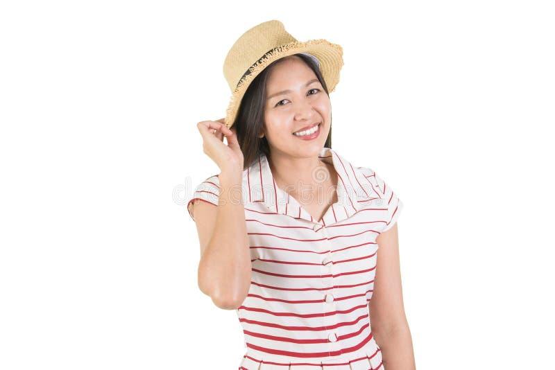 Jeune femme asiatique de sourire heureuse touchant son chapeau de paille photographie stock
