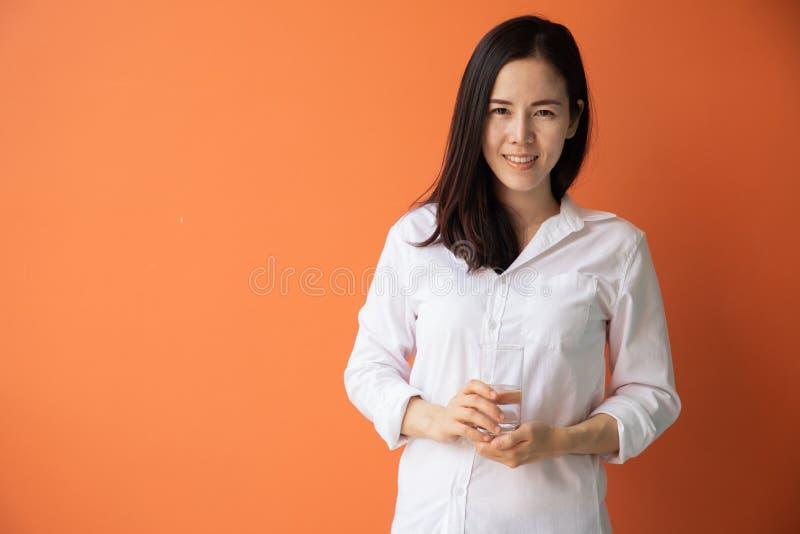 Jeune femme asiatique de sourire tenant des verres de l'eau sur le fond orange d'isolement images libres de droits