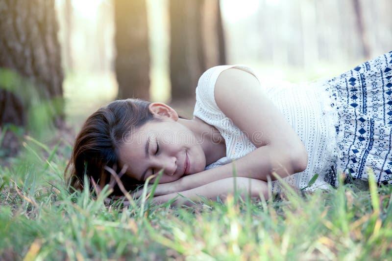 Jeune femme asiatique dormant et se couchant sur l'herbe photographie stock libre de droits