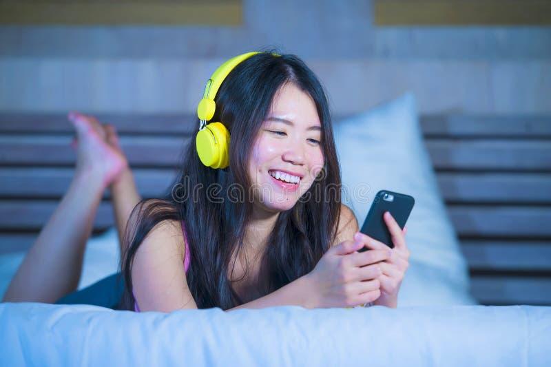 Jeune femme asiatique douce et heureuse du Chinois 20s écoutant la musique image libre de droits