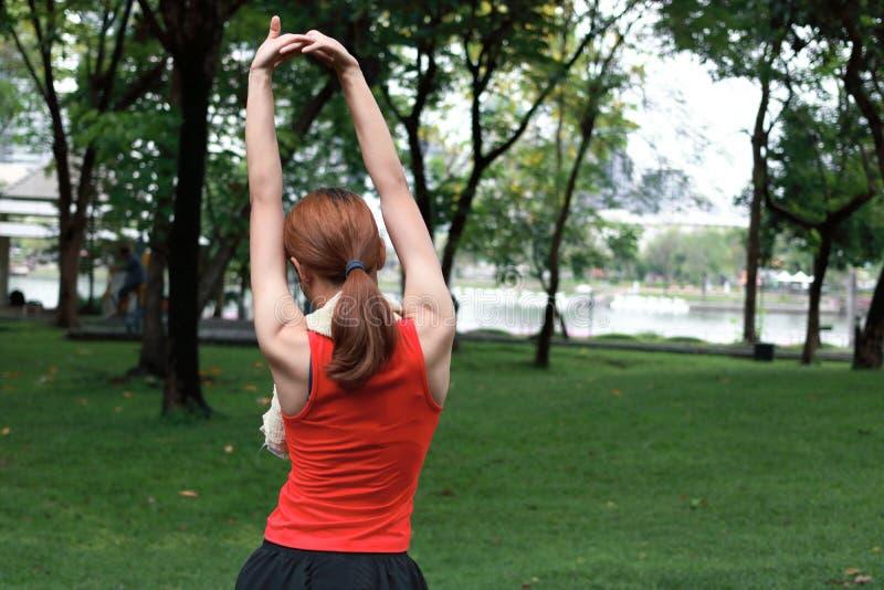 Jeune femme asiatique en bonne santé étirant ses mains avant course en parc dans le matin Séance d'entraînement et concept d'exer images stock