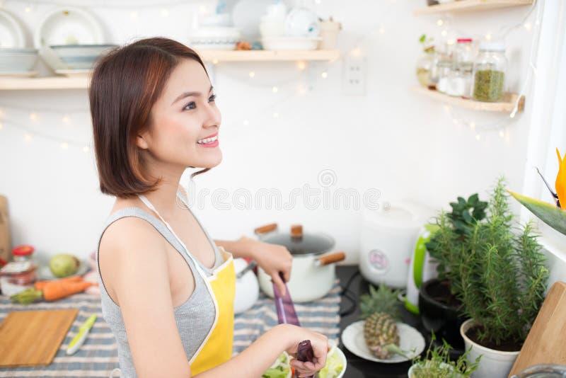 Jeune femme asiatique faisant la salade dans la cuisine souriant et riant h photo stock