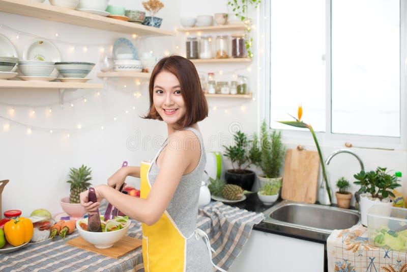 Jeune femme asiatique faisant la salade dans la cuisine souriant et riant h photo libre de droits