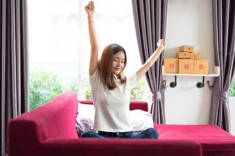 Jeune femme asiatique heureuse d'affaires s'asseyant sur le sofa rouge et ?tirant le bras dans sa maison pendant le matin Affaire image libre de droits