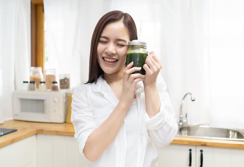 Jeune femme asiatique heureuse de sourire buvant du jus de légumes vert cru frais de detox à la maison Consommation, régime et mo photo stock