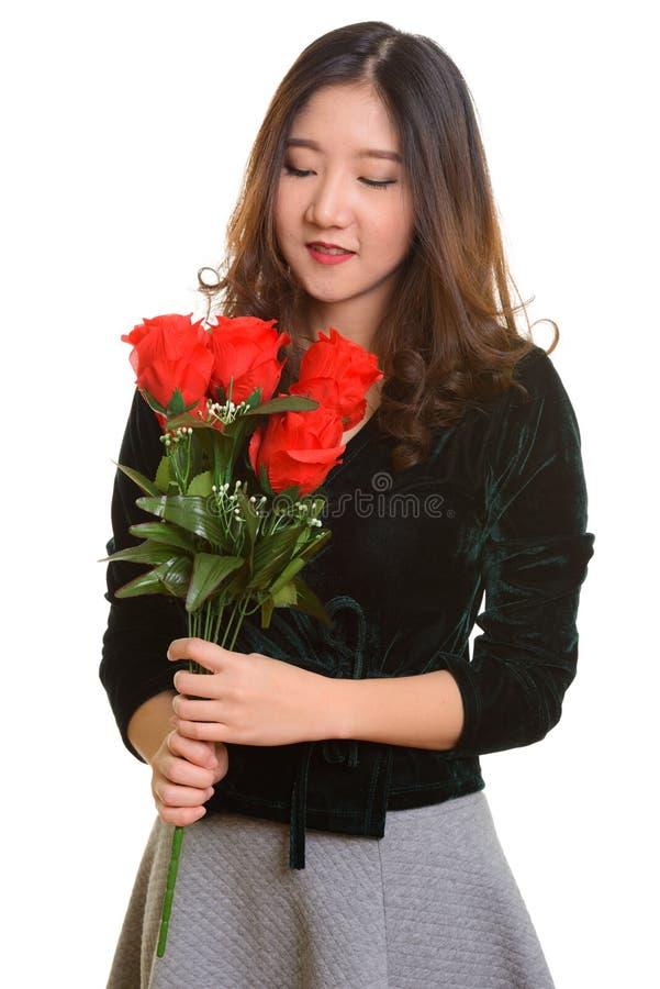 Jeune femme asiatique heureuse jugeant les roses rouges prêtes pour Valentine photographie stock libre de droits