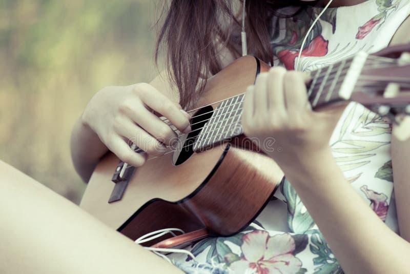 Jeune femme asiatique jouant le guitalele acoustique image libre de droits