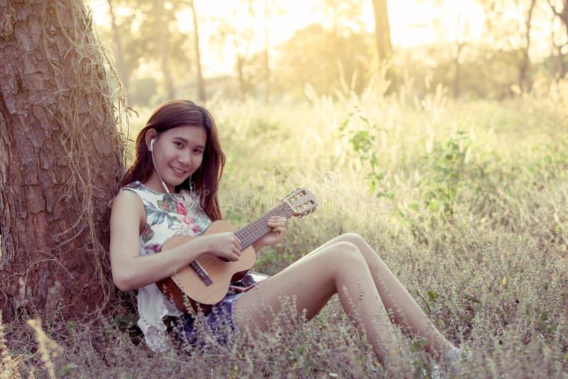 Jeune femme asiatique jouant le guitalele acoustique photographie stock libre de droits