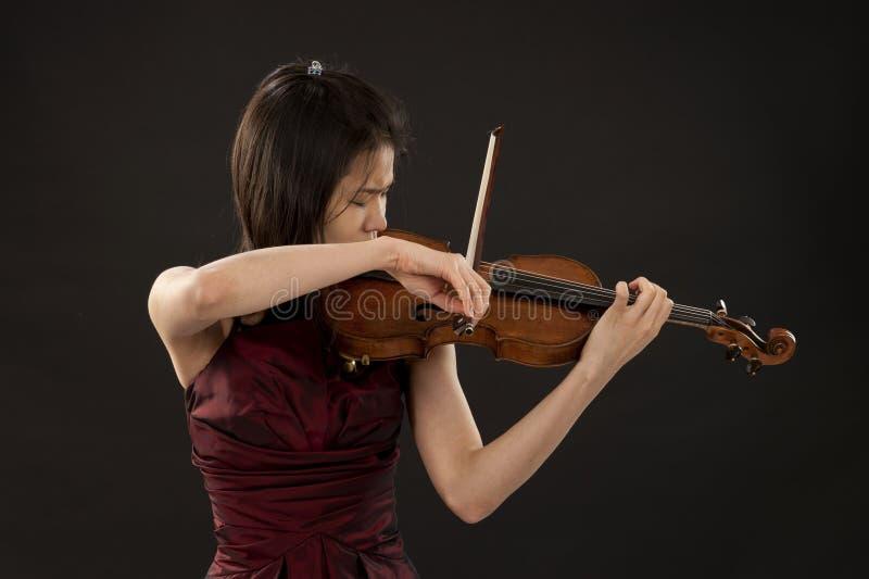 Jeune femme asiatique jouant le violon sur le noir photo libre de droits